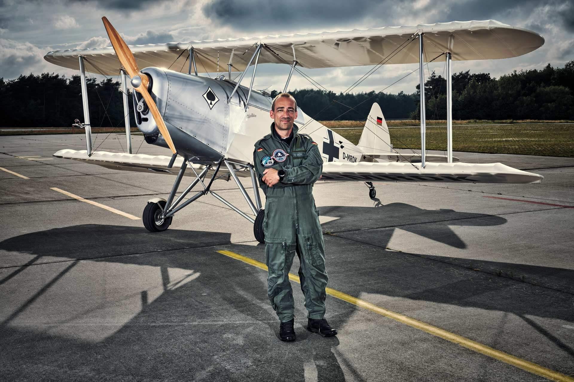 Pilot steht vor seinem Doppeldecker