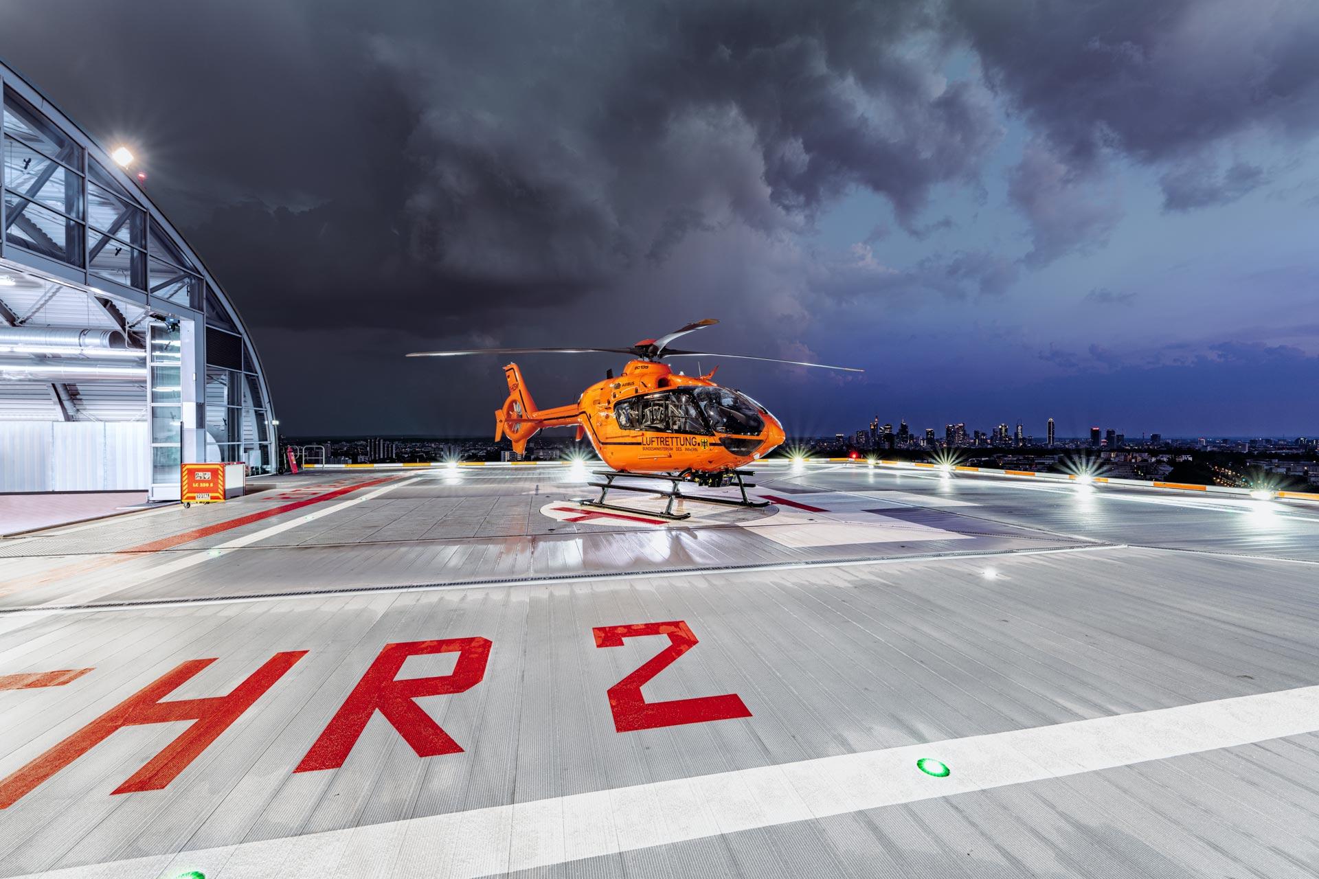 Hubschrauber neben Hangar vor der Frankfurter Skyline